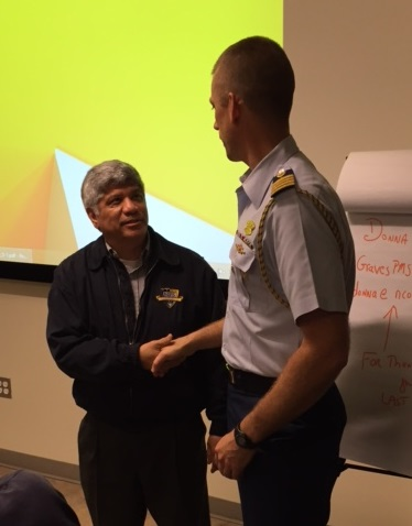AMU professor Dr. Eduardo Martinez shakes hands with USCG Captain Michael Dickey, Deputy Commander of the USCG Cyber Command after presenting student research and recommendations about how the USCG can enhance maritime cybersecurity at the USC campus.